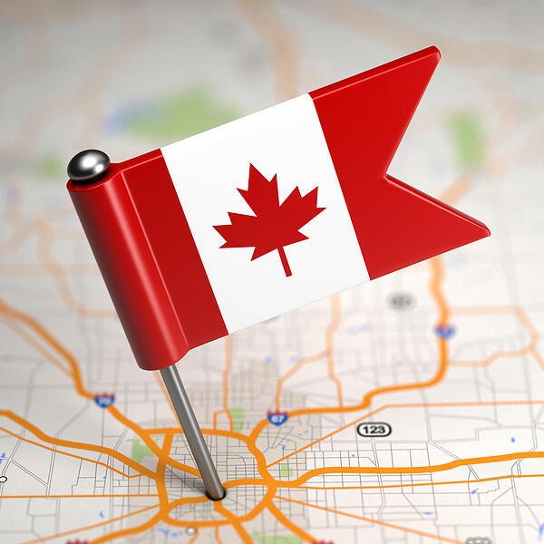 Small Flag of Canada on a Map Background with Selective Focus.